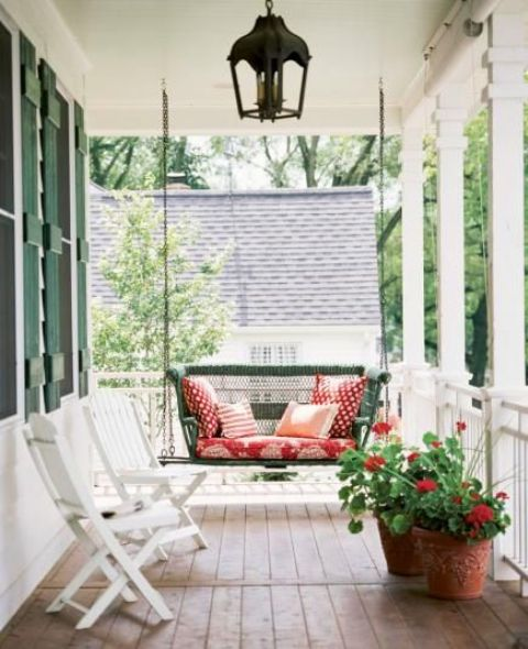a dark green wicker swing with red printed cushions and pillows makes this porch super welcoming