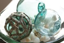 04 a glass bowl with fishing floats and shells is a simple bathroom display