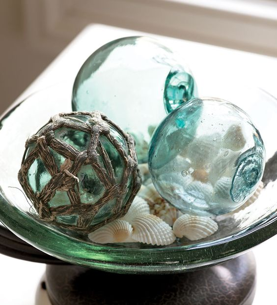a glass bowl with fishing floats and shells is a simple bathroom display