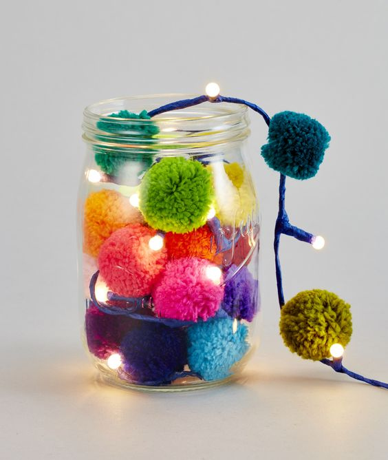 a jar with a garland of colorful pompoms and LED lights for summer decor