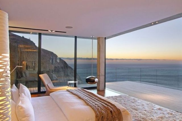 a modern bedroom with glazed walls that offer ocean and mountain views