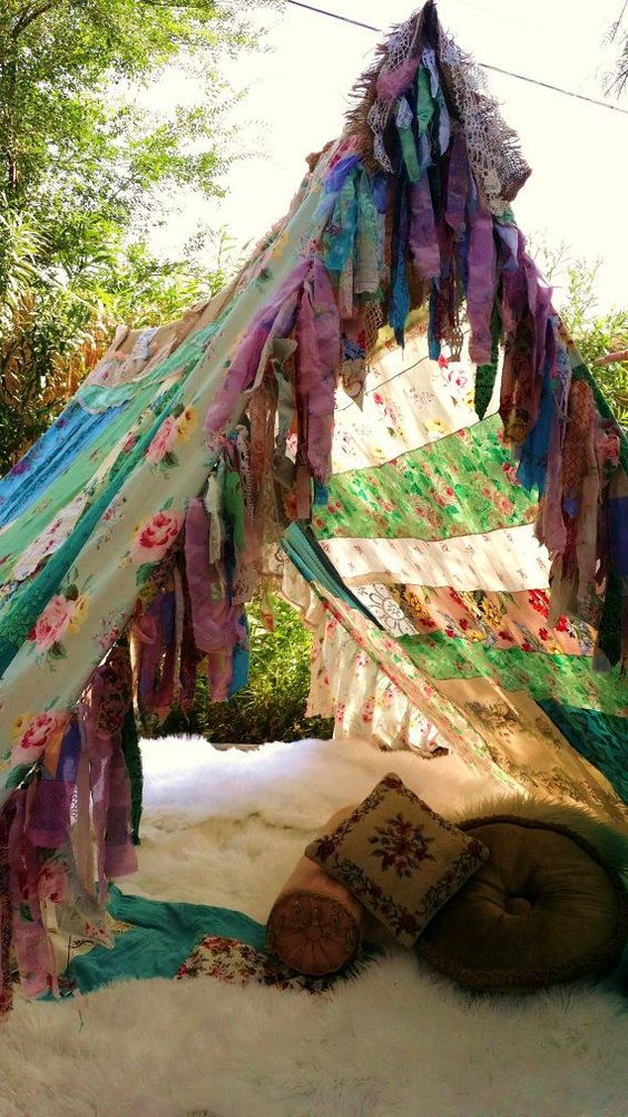 colorful patchwork boho tent with a faux fur blanket and fringe, a couple of pillows
