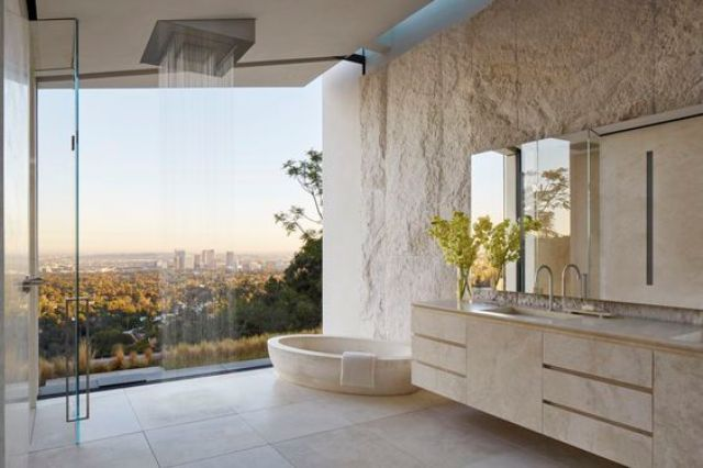 open bathroom concept with a glass wall that overlooks the woodland and the city on the distance