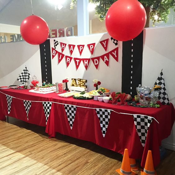 racing cars-themed dessert table with balloons for a boy's party
