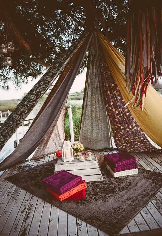a boho teepee on the deck of differnet textiles, colorful cushions and a pallet coffee table