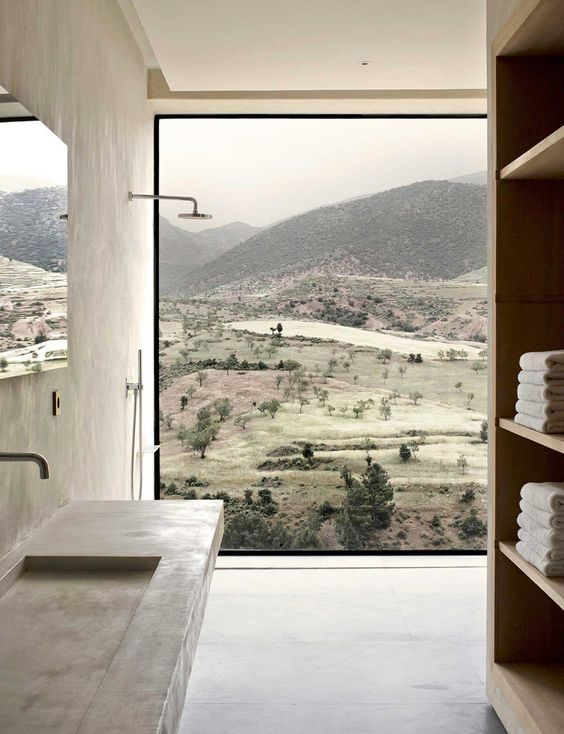 a minimalist bathroom with a glazed wall that overlooks woodlands and hills