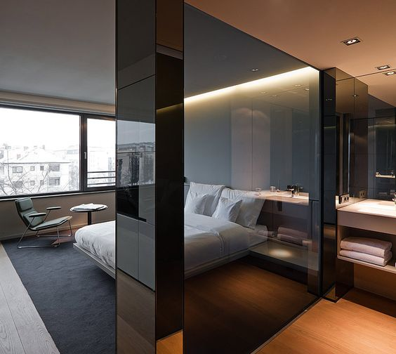 a minimalist bedroom separated with a smoked glass partition from the bathroom