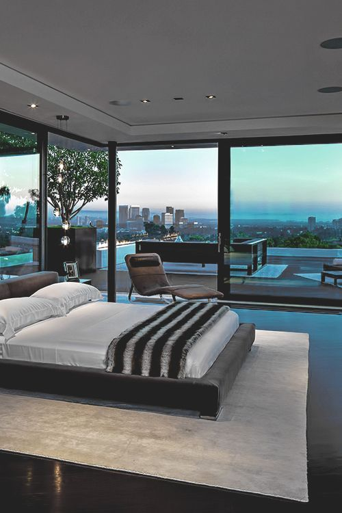 a modern fully glazed bedroom with cool big city views seems to be integrated in the landscape