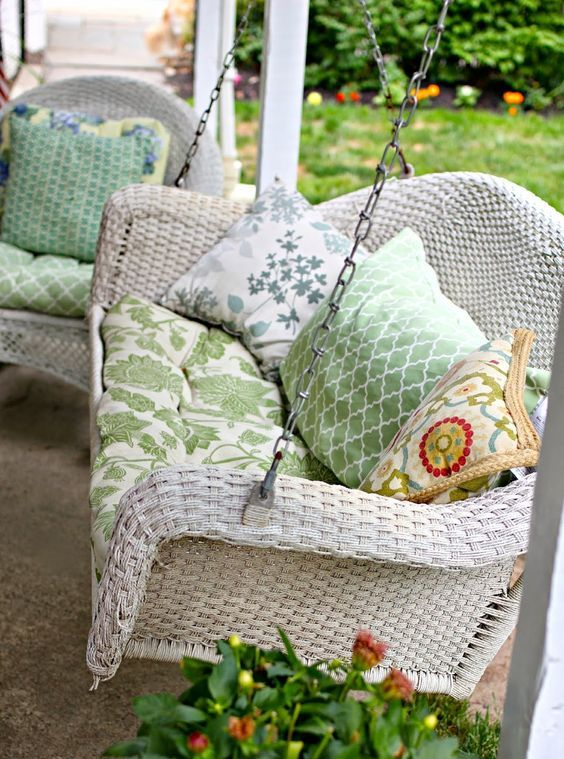 a whitewashed wicker swing with green upholstery for relaxing on your porch after a long day