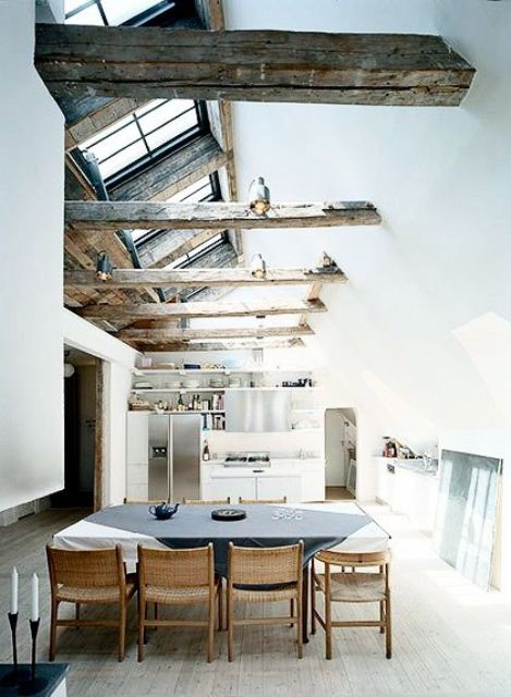 rough wooden beams and black framed window skylights give the space a character