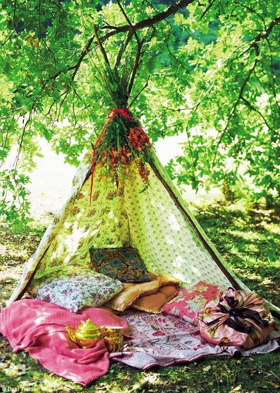 a boho teepe with herbs and flowers, colorful pillows and blankets