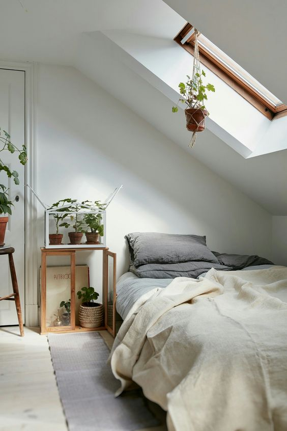 a cozy natural attic bedroom with a skylight lets enjoying sunlight in the morning