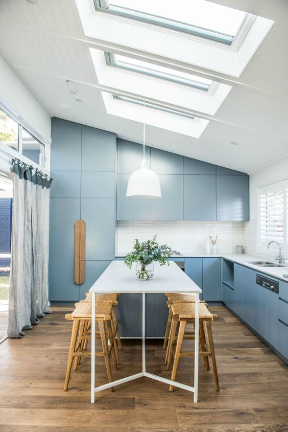 a modern blue kitchen and dining space are lit with the help of skylights