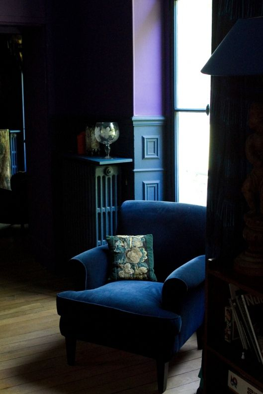 a moody navy velvet chair will fit a dark and decadent space