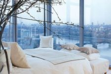 a neutral bedroom with glass walls provides amazing city views, which become the focal point