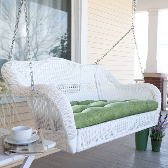 a white wicker swing is a traditional piece for a porch, and it makes it welcoming and peaceful, and your rest joyful