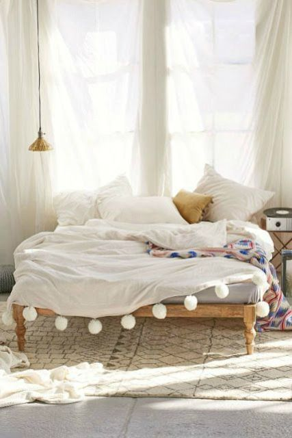 a bedspread with white pompoms to add cheer to your bedroom