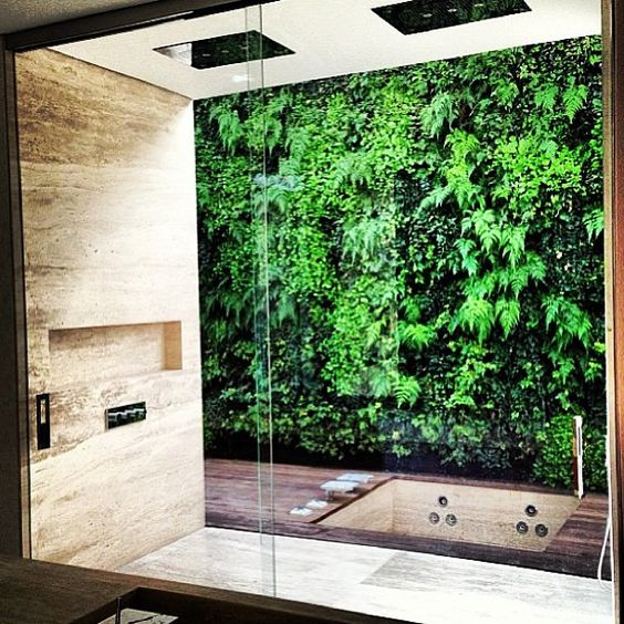 a glazed wall and a living wall outside lets you feel having a shower outside and without anybody's eyes