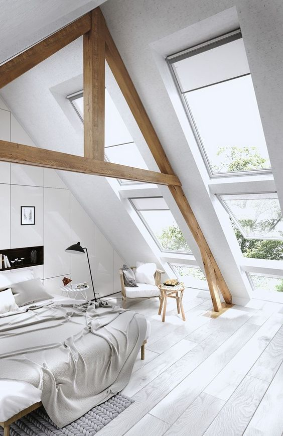 a large Scandinavian bedroom with large window skylights that highlight the double height ceiling