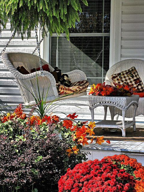 a white rattan furniture set including a swing with colorful fall textiles for a welcoming porch