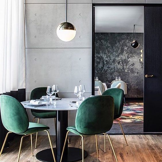 emerald velvet chairs with copper legs stand out in a minimalist dining space with concrete walls