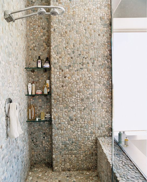 the bathroom completely covered with pebble tiles looks unusual and creative