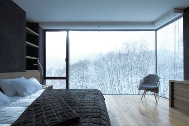 two glass walls offer amazing forest views, which perfectly complement this laconic masculine bedroom