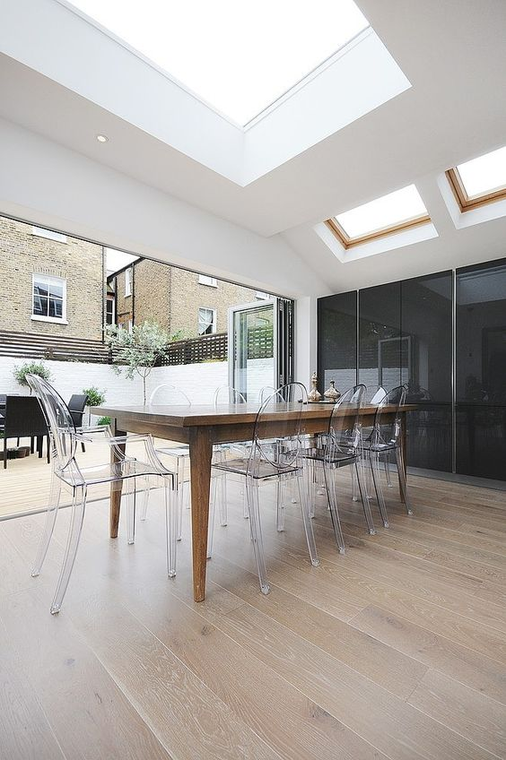 a modern dining space with a rustic dining table and acrylic chairs, a large window-like skylight makes it light-filled
