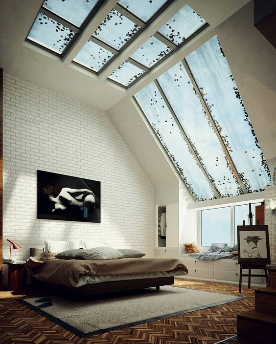 an industrial bedroom with large windows coming into skylights and then a glazed ceiling to flood the space with light