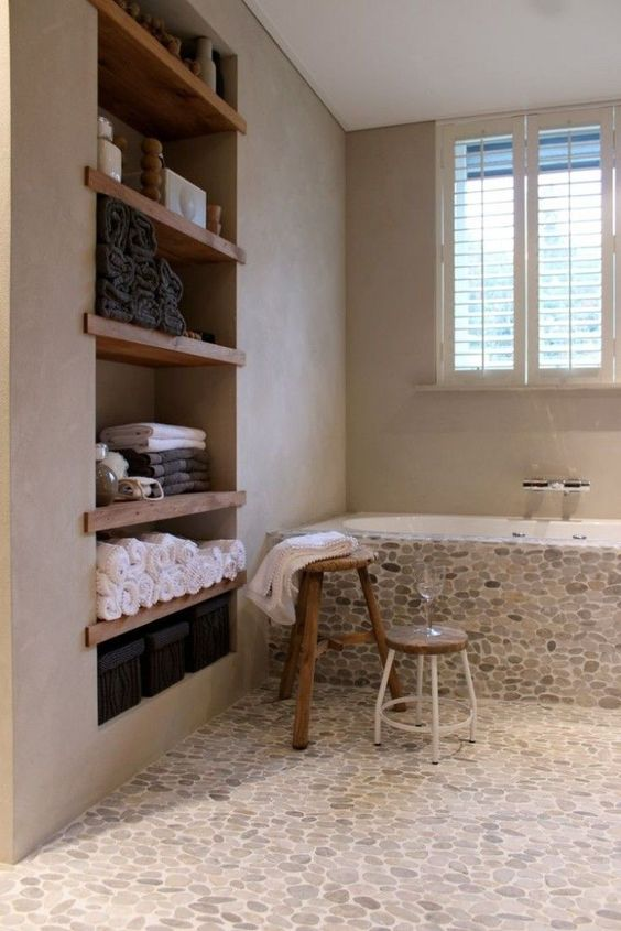 the bathroom floor and bathtub covered with pebble tiles and concrete walls for a chic look