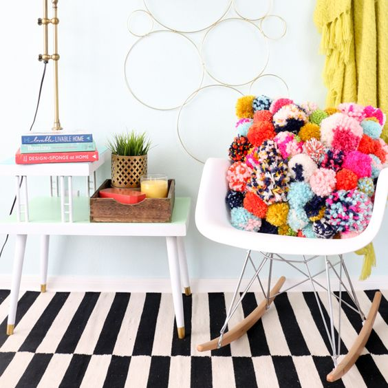 a colorful pompom throw pillow will spruce up your space for summer and make it bolder