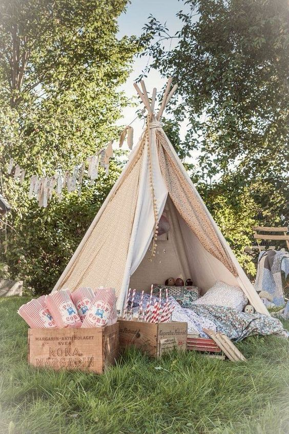 a neutral fabric teepee for kids, with printed pillows and blankets and a pompom trim