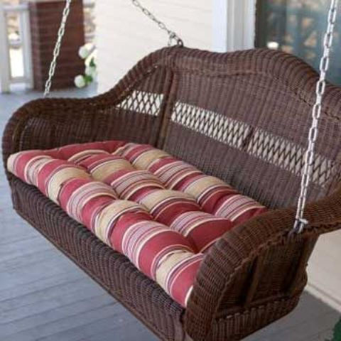 a traditional wicker swing in brown with comfortable striped upholstery