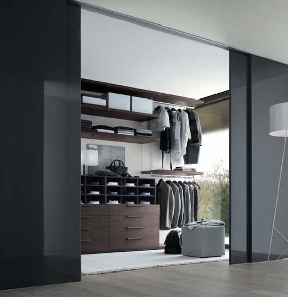 hide your walk-in closet behind smoked glass sliding doors to keep the space modern and masculine