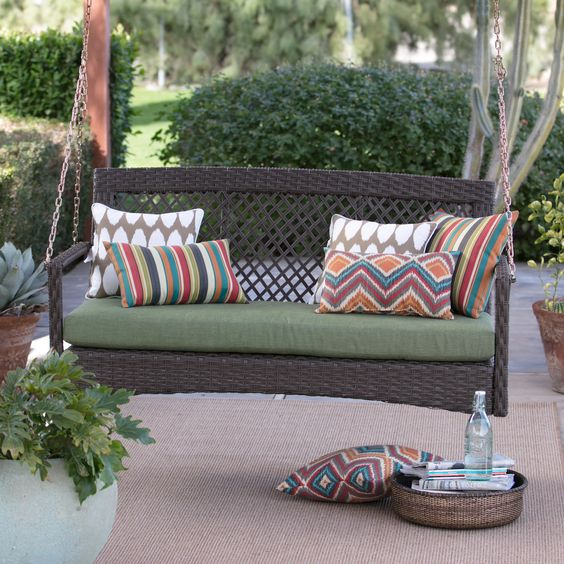 a brown resin rattan porch swing with colorful boho pillows will enliven any space