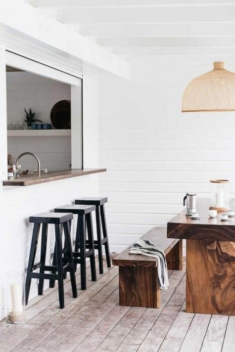 a cozy white pass through space with a narrow windowsill and black stools plus a real dining zone
