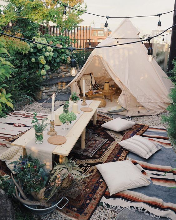 a neutral teepee in the backyard, with a small wood coffee table, and a picnic setting