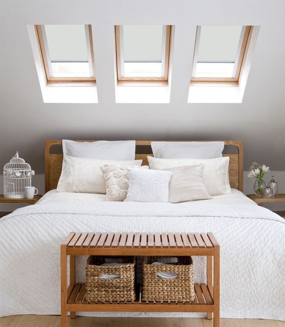 a small attic space with three skylights instead of a headboard is a nice idea to get natural light