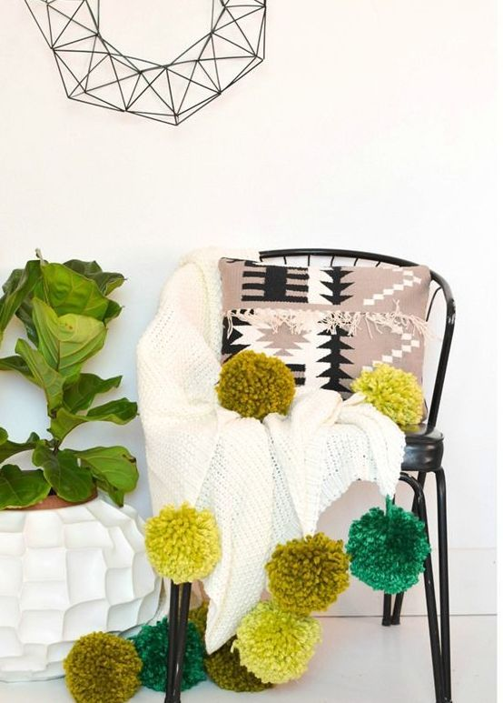 a white crochet blanket with large bold green pompoms if the night is cold