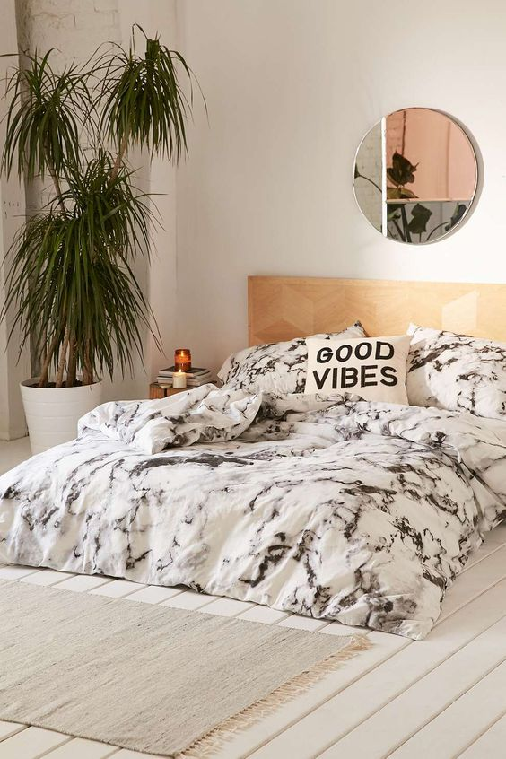 black and white marble bedding and a copper mirror make the bedroom really chic