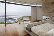 10 cozy bedroom with a stone hearth and a glazed wall that provides amazing ocean views