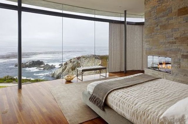 cozy bedroom with a stone hearth and a glazed wall that provides amazing ocean views