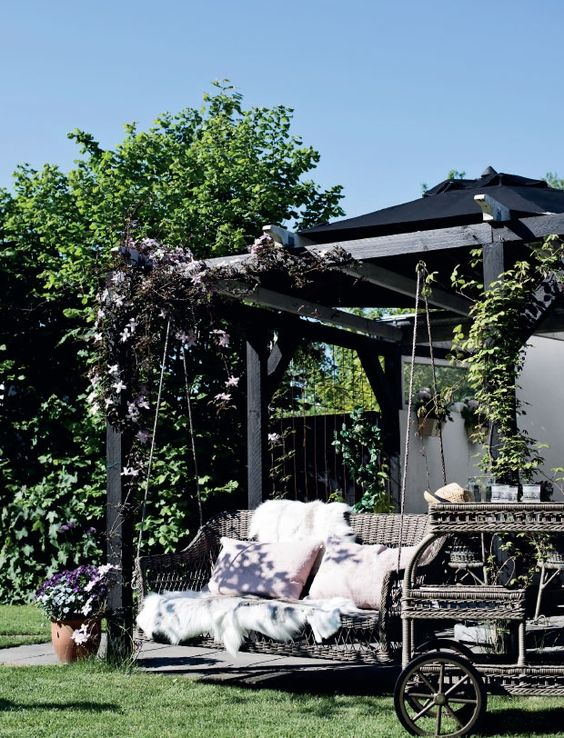 a cozy arbor with a rattan swing and lots of pillows and a matching rattan bar on wheels