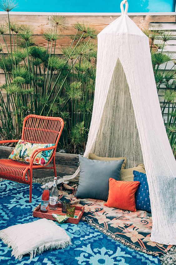 a sheer teepee with a couple of pillows to complement a boho chic terrace