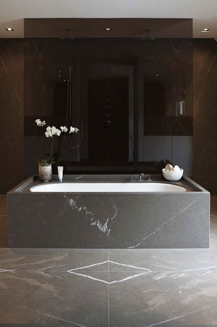 black marble bathroom feels luxurious, and a smoke glass shower adds style