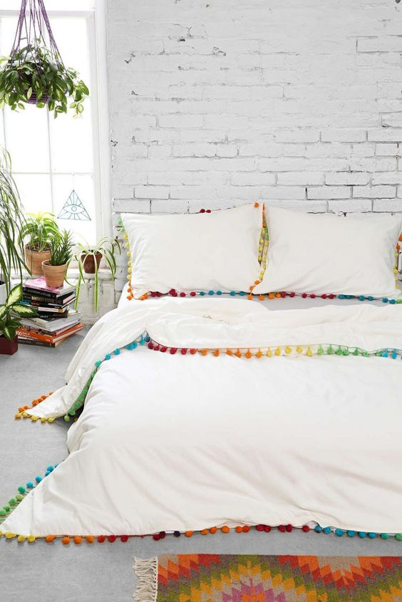 colorful pompoms lining the bedding automatically makes it summery