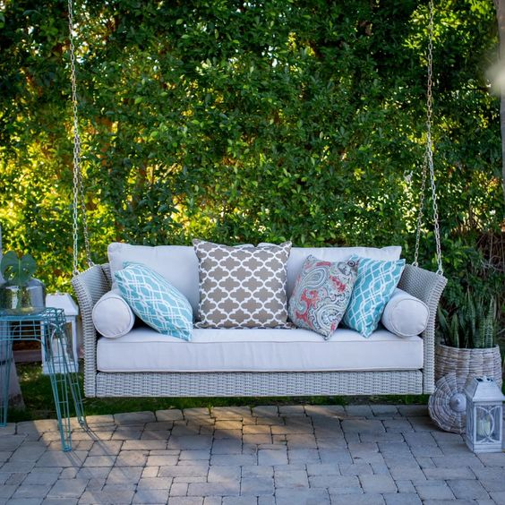 a light grey wicker swing with printed pillows will fit any modern backyard
