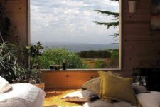 12 a rustic bedroom with a large window that offers woodland and sea views