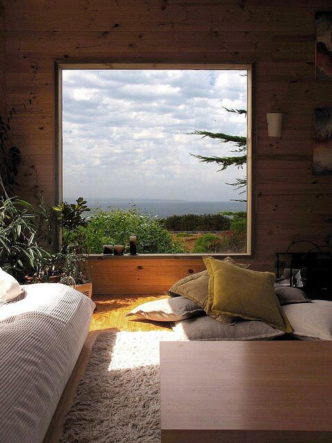 a rustic bedroom with a large window that offers woodland and sea views