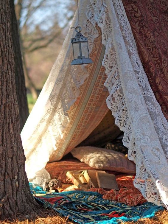 a small cozy teepee with a lace cover, colorful printed blankets and pillows hidden in between the trees